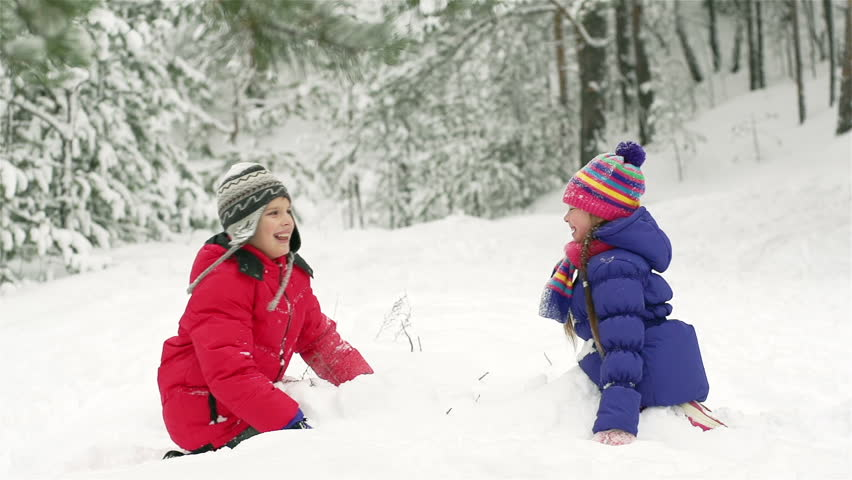 Slow-motion of joyful kids playing in snow fighting with each other