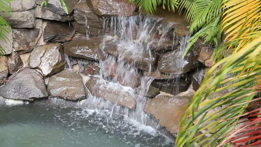 Water falling on rocks and slate in a poolside water feature. - HD stock video clip