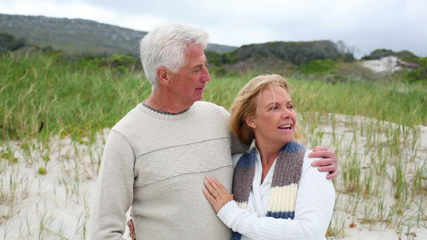 Smiling retired couple standing on the beach on a windy day - HD stock footage clip