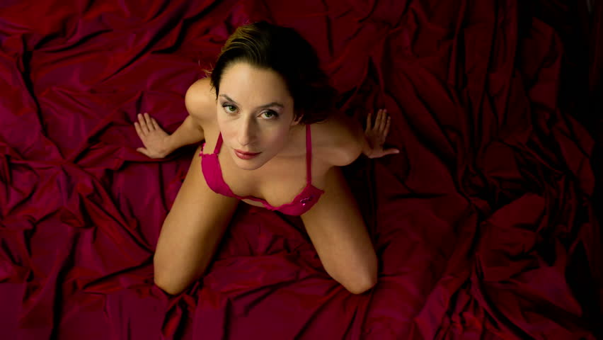 beautiful woman moves and poses on a bed.  - HD stock video clip