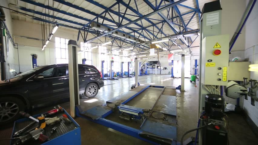 Car in modern workshop of Service station with lift and other equipment - HD stock video clip