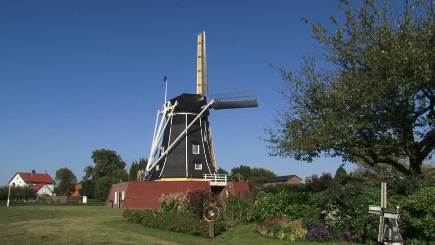 Black tarred beltmolen-type windmill in operation - Side view + scale model windmill in garden. WINTERSWIJK, THE NETHERLANDS  - HD stock footage clip