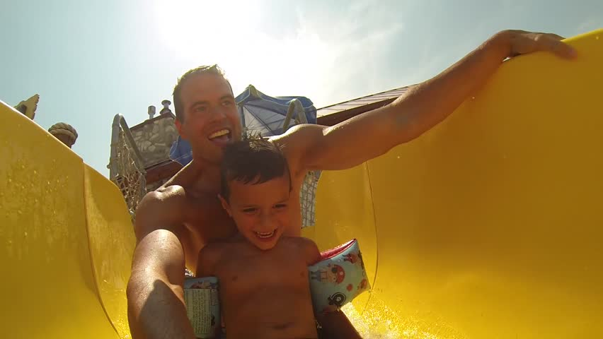 Attractive athletic and healthy father going down a bright colored water slide with his young son and a clear beautiful Summer afternoon.  - HD stock video clip