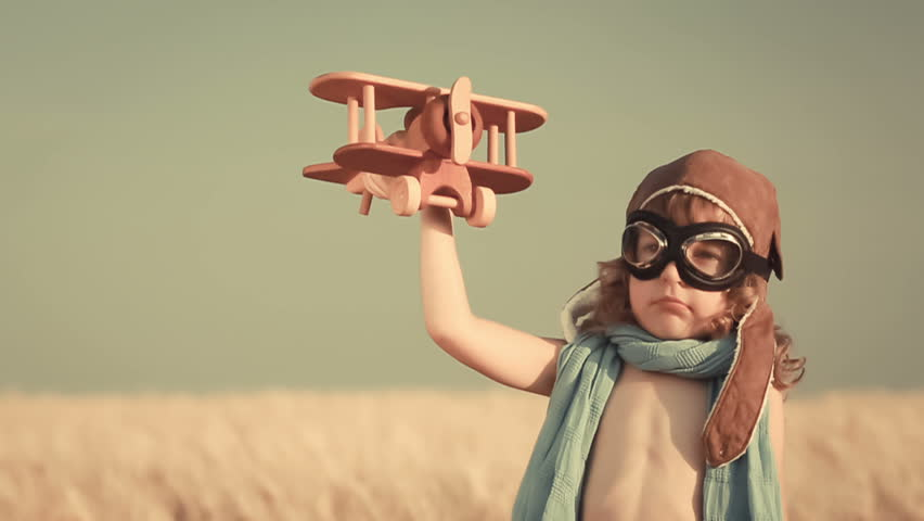 Happy kid playing with toy airplane against summer sky background | Shutterstock HD Video #5541338