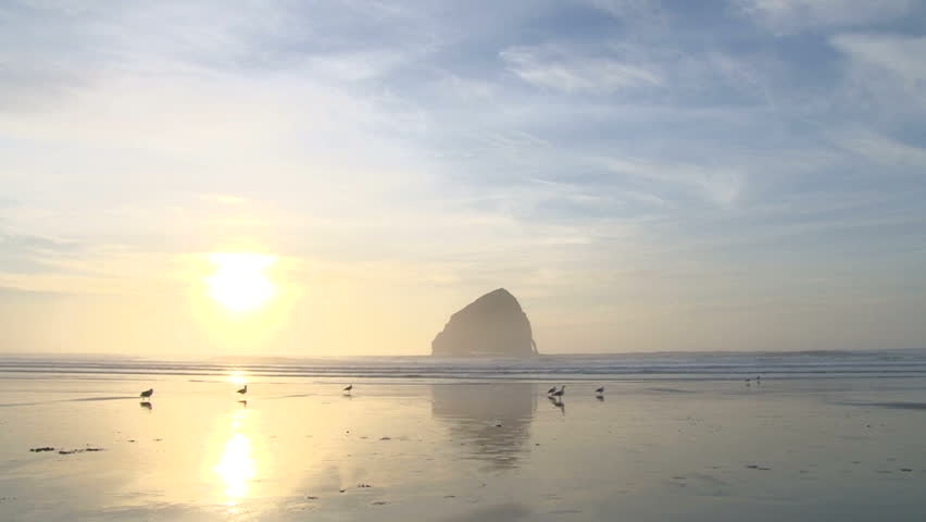 Time lapse of sun setting behind horizon on beautiful ocean beach with seabirds flying.