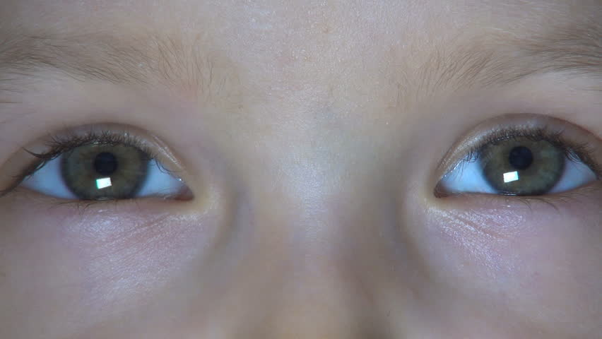 Girl with blue eyes peering out from behind curtain of wet