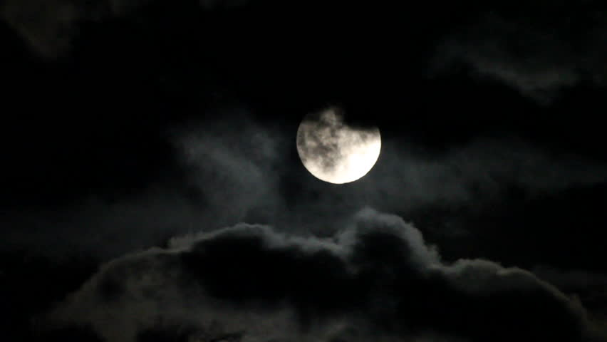 Dark night sky with a full moon shining bright as clouds move across the face of the moon. - HD stock video clip