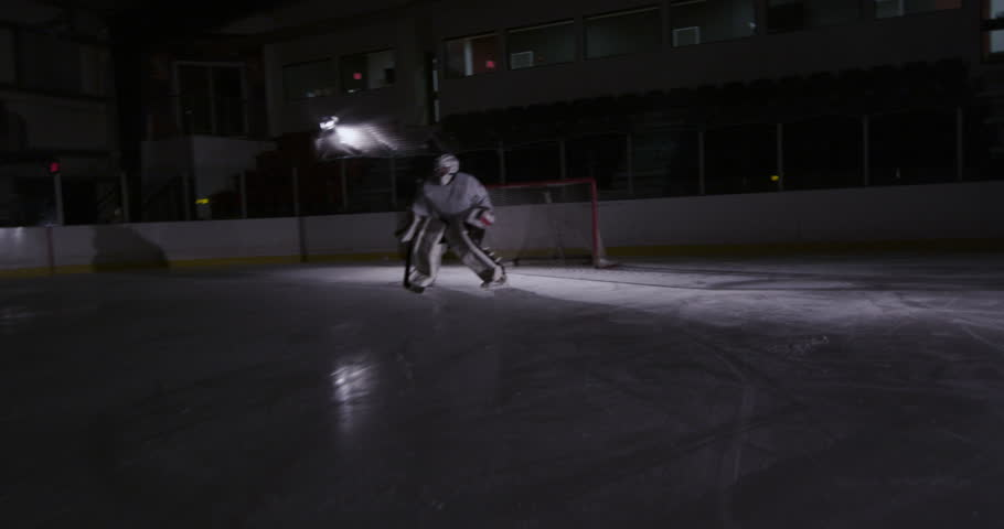 Hockey Player Rushing up the Ice to shoot puck on goalie - 4K stock footage clip