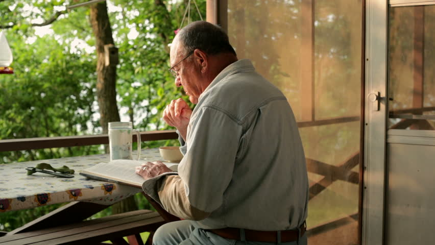 Senior man, relaxing and reading a book, while sitting outside in front of a cabin on a lake. - HD stock video clip