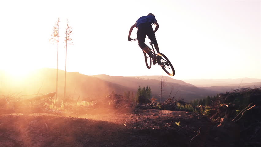 Mountain biker jumping at sunset in super slow motion | Shutterstock HD Video #5566250