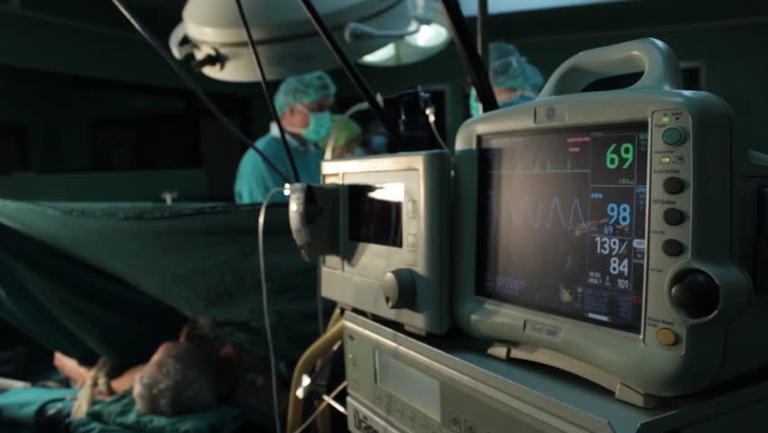 Srbija,Krusevac,29.01.2014.Public hospital.Ecg monitor heartbeat, patient with oxygen lying on operating table.Surgeons team performing operation in hospital operation theater,out of focus.