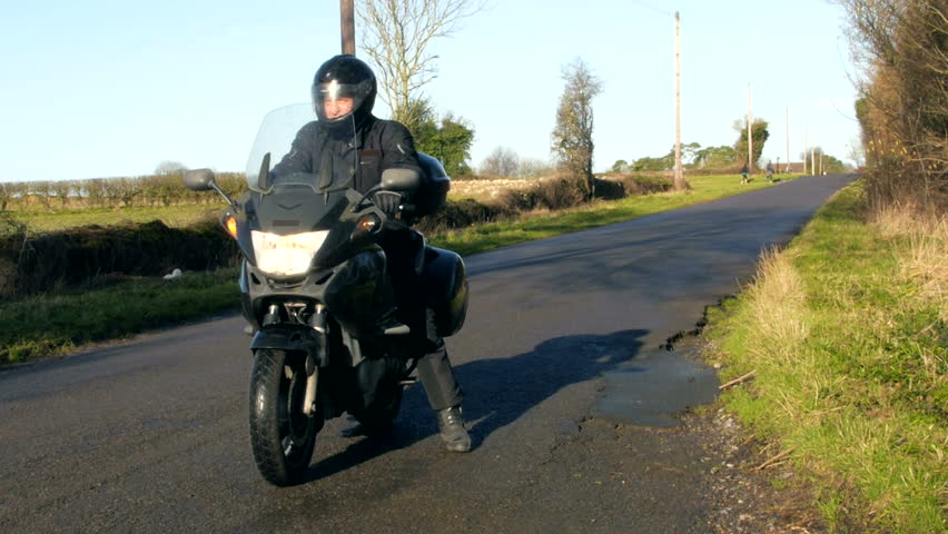 A motorbike rider stalls his bike on country road on sunny windy day. Epic fail. Model release on file.