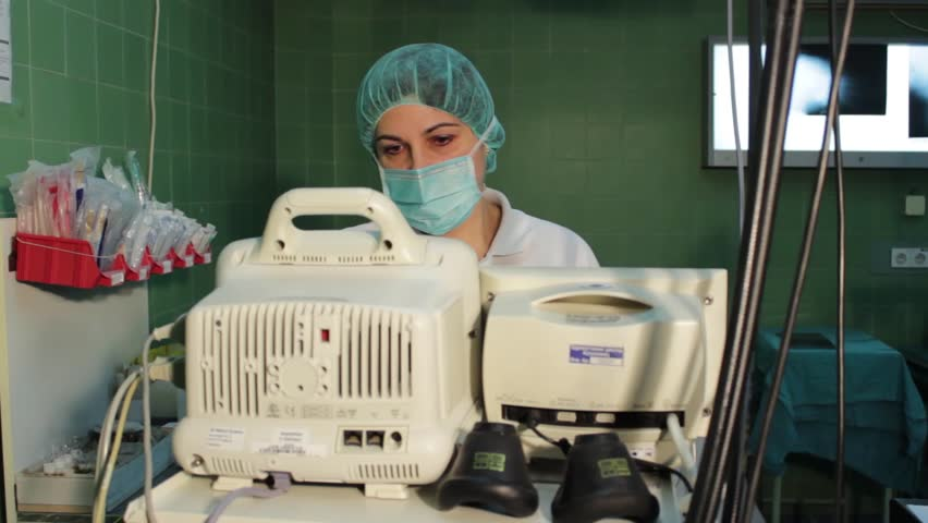 Surgeons team preforming operation in hospital operating theater.Anesthesiologist watching ecg monitor, close up face,wearing mask,checking patient.