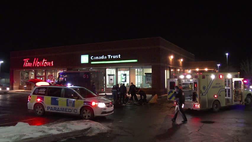 MONTREAL, QC - JAN 2014 - 4K UHD - Paramedics doing CPR at a bank. Team of paramedics and police officers are working on a victim of a shooting doing CPR with armored car and bank in the background.