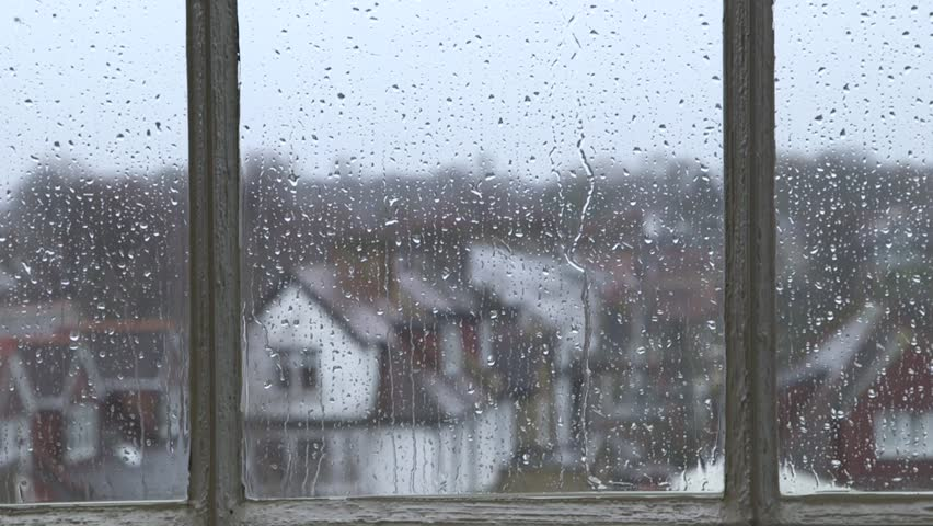 Heavy rain falling against large window pane, raindrops trickle down, grey sky with London houses outside | Shutterstock HD Video #5625488