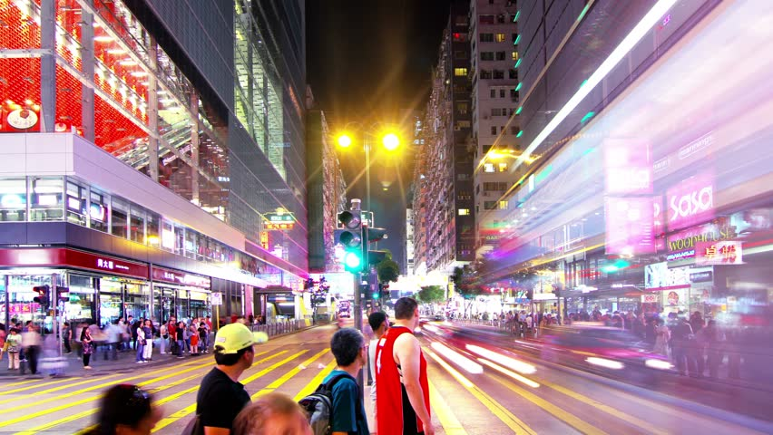 Tsim Sha Tsui. Hong Kong Night Timelapse. 4K Tight Static Shot. Office buildings with commercial billboards. Busy traffic on the main road. Traffic lights flashing and people crossing roads.