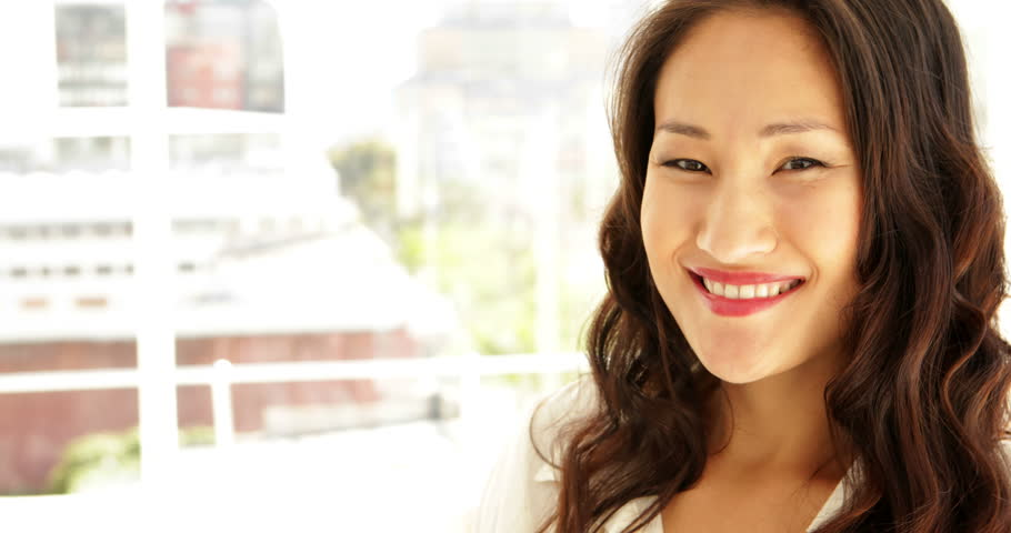 Asian businesswoman smiling at camera with arms crossed at the office - 4K stock video clip