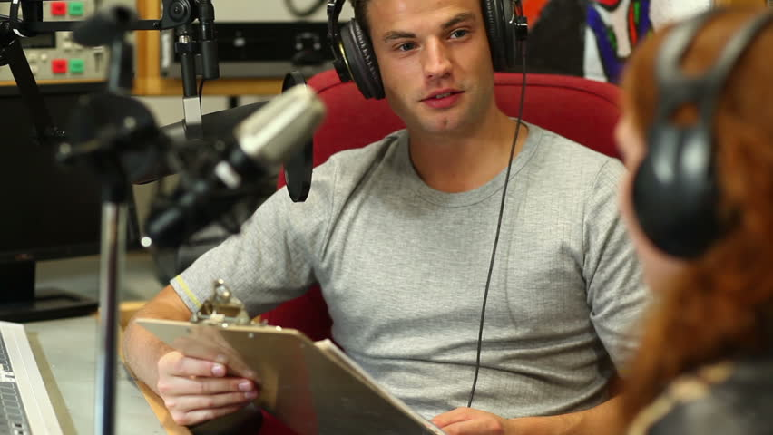 Handsome student interviewing someone for radio in the studio at the university