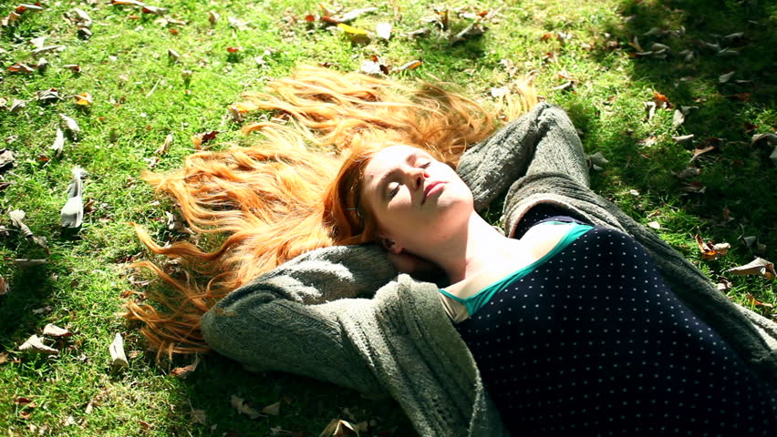 Young redhead relaxing on lawn in bright sunshine | Shutterstock HD Video #5660768