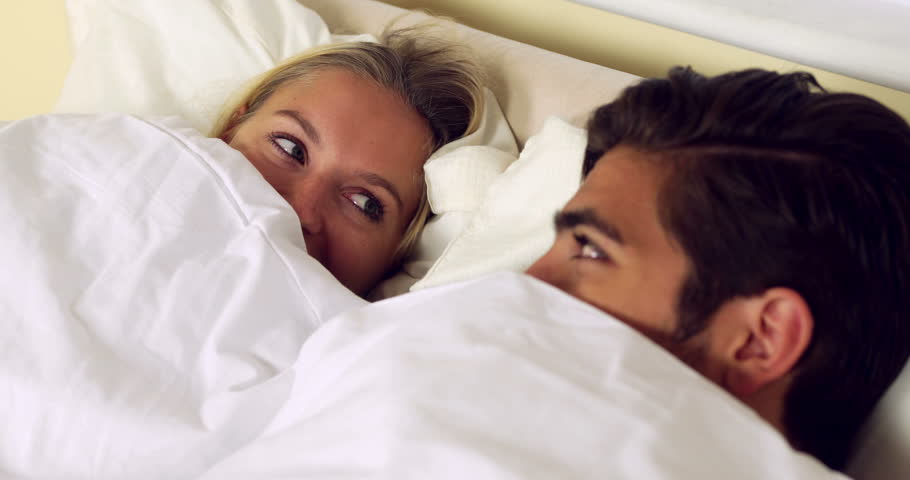Cute Young Couple Asleep Together On Bed At Home In