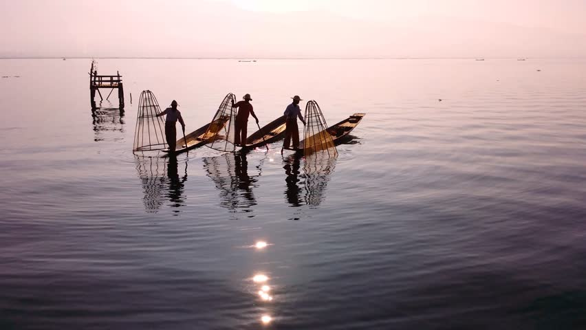 Myanmar, Burma Inle Lake fishermen fishing on traditional boat at sunset. Beautiful reflection of evening sun and silhouettes in water. Famous tourist travel destination 4k ultra high definition video - 4K stock footage clip