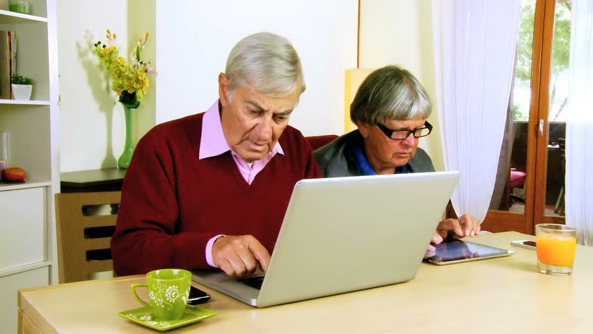 Serious senior couple working with pc and tablet at home - HD stock video clip