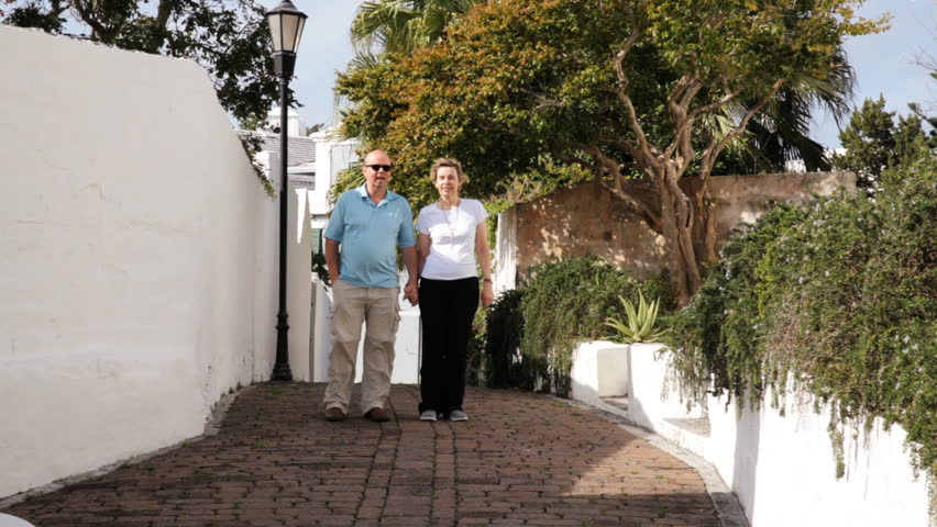 Middle aged couple casually dressed walking on a small street in St George's Bermuda in the afternoon sun - HD stock footage clip