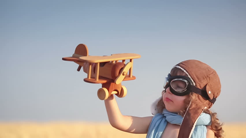 Happy kid playing with toy vintage airplane against summer blue sky background. Travel concept. Slow motion | Shutterstock HD Video #5712365
