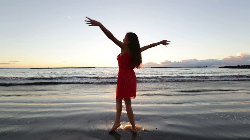 Beach woman having fun spinning around dancing at sunset enjoying freedom during summer holidays vacation travel. Beautiful happy young mixed race Asian Caucasian female model outside. - HD stock video clip