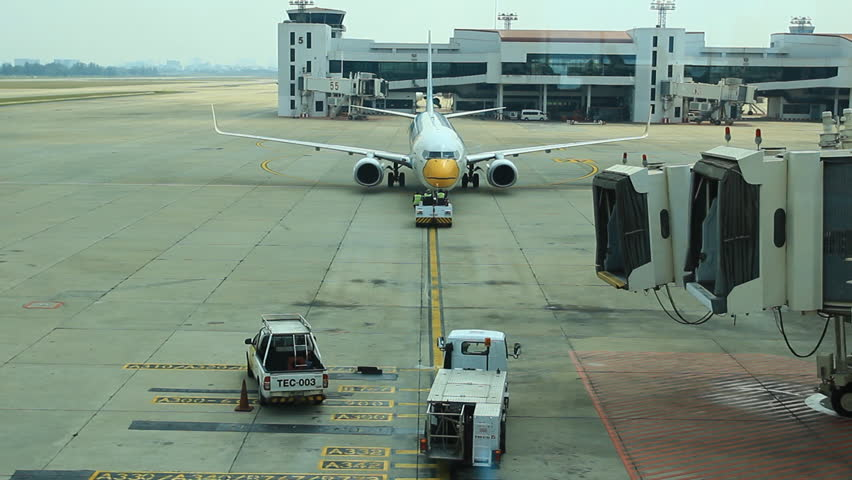 BANGKOK THAILAND - FEBRUARY 28, 2014 : Nokair airplane workers  busy utility vehicles around parked airplane,on FEB 28,2014 in Don Muang Airport Bangkok Thailand - HD stock video clip