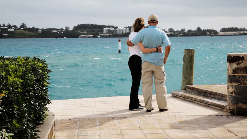 Rear view of happy man and woman walking together at for Awesome vacations for couples
