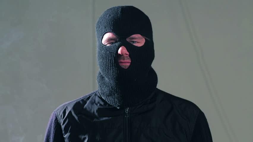 Masked criminal smoking