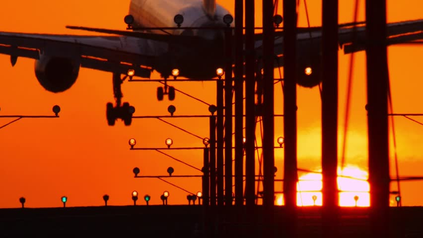 Airplane jet plane landing in airport at sunset, flying into sun. Slow motion. | Shutterstock HD Video #5818718