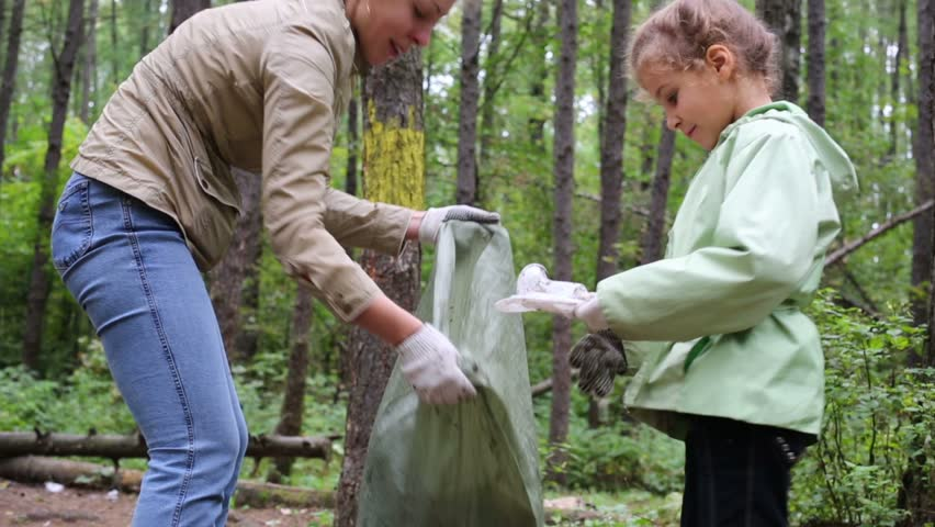 Mother with daughter helping clean up green forest - HD stock video clip