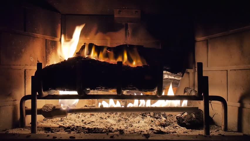 Wide shot of a yule log burning in a fireplace.