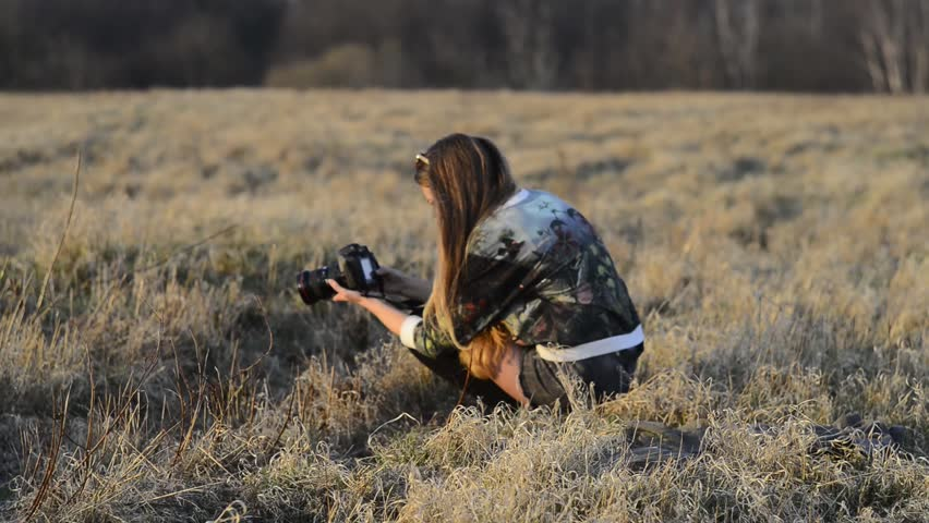 Young girl sitting/knee-bend on dry grass with camera