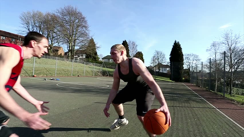 Friends playing basketball outdoors with one player easily defeating the defense and slam dunking - HD stock video clip