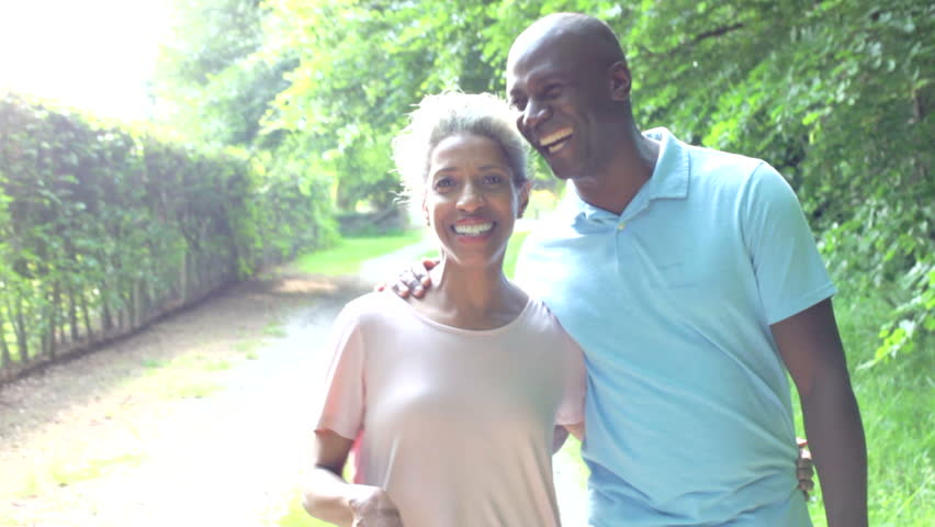 Mature African American couple walking along country track towards camera.Shot on Canon 5d Mk2 with a frame rate of 25fps