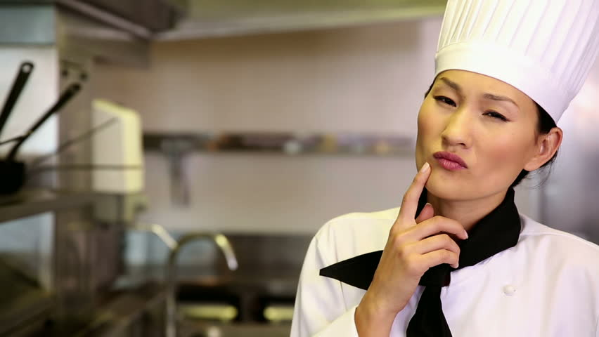 Thoughtful chef smiling at camera in commercial kitchen - HD stock video clip