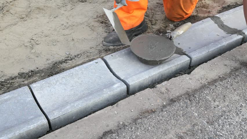 Granite Curb Pricing : Worker installing curb stone using trowel and mortar