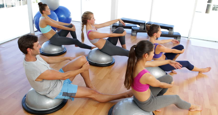 Fitness class lying on bosu balls together at the gym - 4K stock footage clip