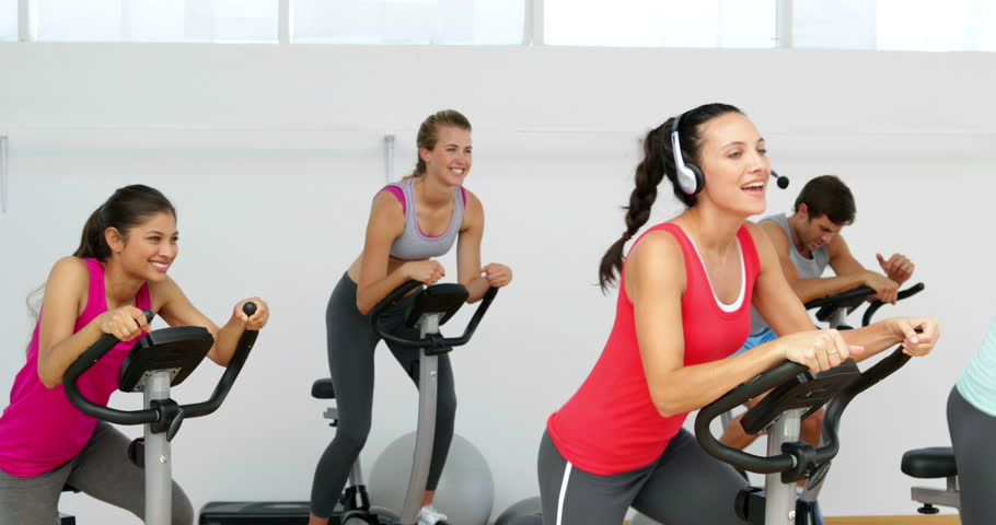 Spinning class in fitness studio led by energetic instructor at the gym - 4K stock video clip