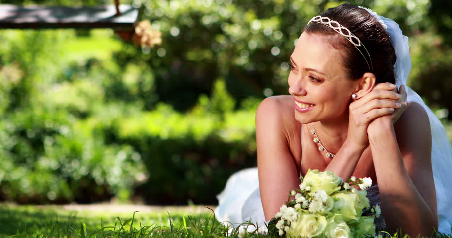 Beautiful bride smiling at camera lying on the grass on her wedding day