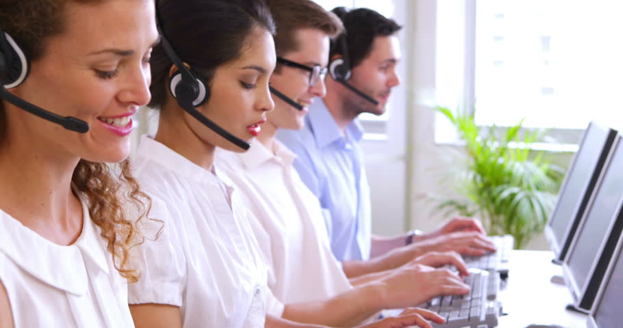 Row of call centre agents typing at their desk in the office