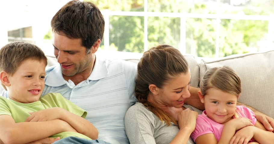 Cute family relaxing together on the couch in living room at home