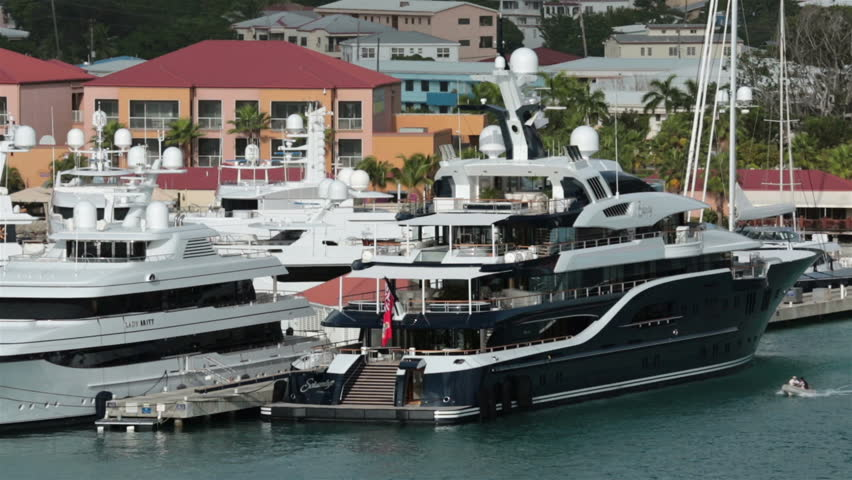 ST THOMAS - JAN 2014: Luxury private yachts in harbor USVI. Main tourism destination. The Solandge at 279 feet charter at $1 million per week. Most registered in Cayman Island. Tourism primary income.