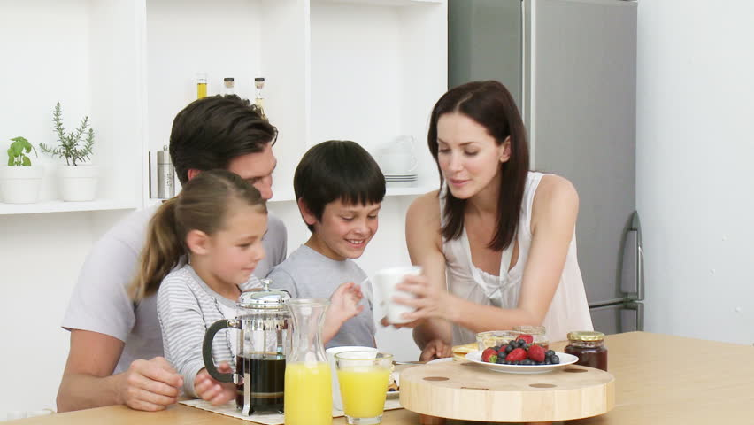Happy young family having breakfast in the kitchen. Nutritive meal. Footage in high definition - HD stock video clip