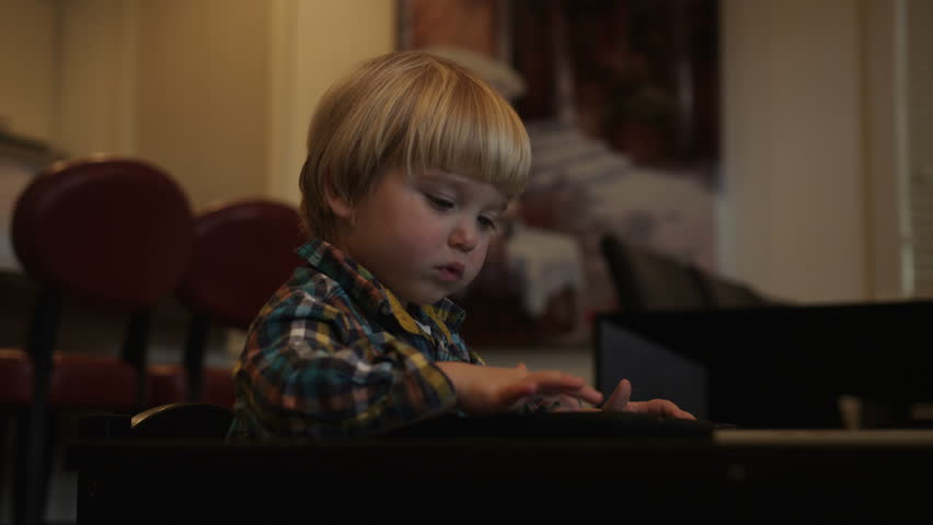 A young boy drags objects around the screen of a tablet while sitting at a small table.