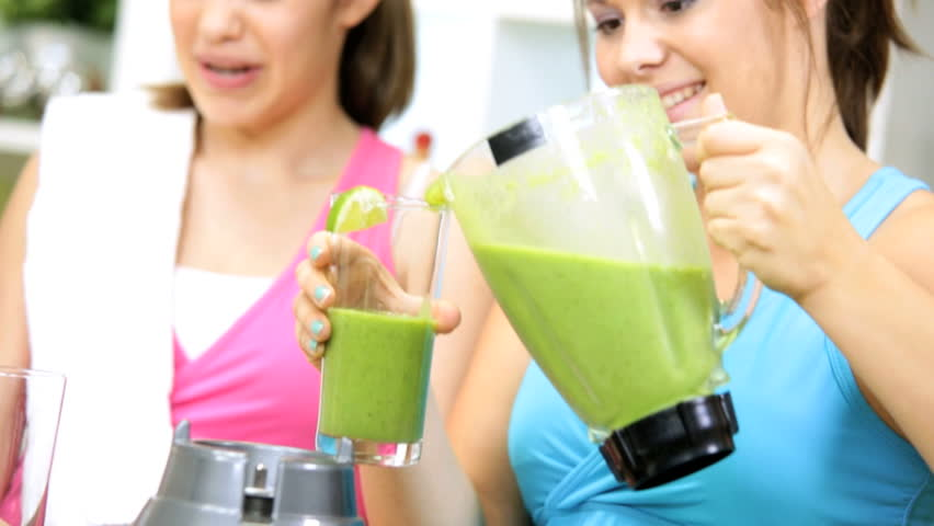 Caucasian family females preparing workout session pouring fresh organic fruit vegetable juice as part modern healthy lifestyle diet - Caucasian Exercise Girls Fresh Blended Vegetable Drink