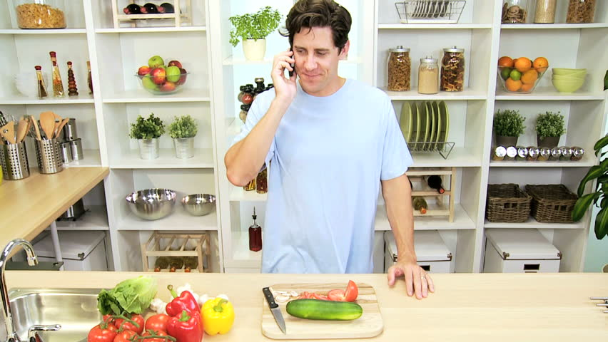 Casually dressed young Caucasian male talking smart phone home kitchen fresh healthy vegetables lunch - Casual Caucasian Male Smart Phone Home Kitchen - HD stock video clip